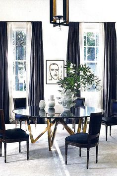 Dramatic black, white and gold dining room with sculptural modern pieces mixed with traditional fabrics.