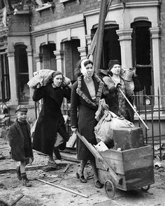 Bombed out: A family walk the streets with their few remaining possessions
