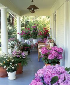 For a fast way to perk up a porch, relocate pots of lush flowers from indoors to out. With a limited palette, like the pink and white blooms here, the collection feels cohesive, not chaotic. Click through for more small garden ideas.