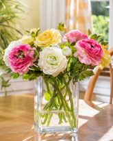 Mixed colors of beautiful ranunculus cuttings in a tall rectangular vase of crystal clear acrylic water will grace your room with garden fresh charm. It's a wonderful silk flower arrangement with casual flair, ideal for sunroom tables and kitchen islands.