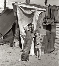 """January 1937. """"Two children of a migrant fruit worker from Tennessee, standing before their temporary home. This family of eight is camped in a field near the packinghouse at Winter Haven, Florida.""""  35mm nitrate negative by Arthur Rothstein for the Farm Security Administration."""