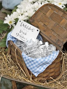 Cradled in an old wheelbarrow, a picnic basket filled with containers of bubbles set out so guests could shower the newlyweds with bubbles.