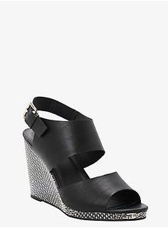 "Enjoy a walk on the wild side. A snake-like pattern gives this black wedge sandal some real attitude. Wide faux leather straps complete this modern look.<ul><li> 4 1/4"" wedge with 1/4"" platform</li><li>Man-made materials</li><li>Imported</li></ul>"