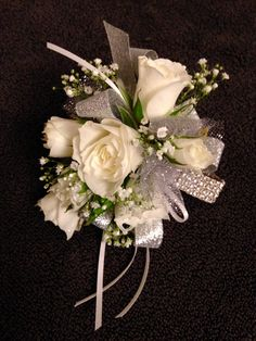 Wristlet corsage using a rhinestone wristlet. White spray roses and babies breath with silver and white ribbon and tulle accents. Floral design by Batbara Colson