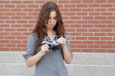 beautiful teenage photographer adjusting her camera. - Beautiful teenage photographer adjusting her camera while standing outdoors, Model: Cassandra Kosmayer