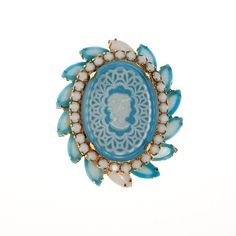 """DESCRIPTION Juliana Cameo BroochTurquoise or Cinderella Blue RhinestonesWhite Milk Glass RhinestonesNavette and Brilliant Round Cut StonesGorgeous Color Combination DETAILS1960s ERAGold tone broochLight blue and white broochCameo in centerExcellent vintage conditionMEASUREMENTS 2.00"""" from side to side2.50"""" top to bottom"""