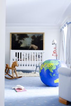 Vincent Frey & Bianca Lee Vasquez,   CEO of Maison Pierre Frey, in Paris (1er arrondissement).  Love both the globe pillow (!) and the very grown up art above the crib. (Photo by Julie Ansiau for The Socialite Family.)