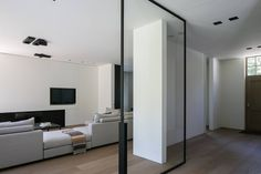 Beautiful large pivoting door with small steel frame. House VM by Dennis T'Jampens. Photo by thomas de Bruyne.