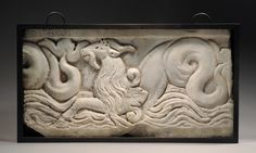 ROMAN MARBLE RELIEF SECTION DEPICTING A CAPRICORN,    A mythical animal with the foreparts of a goat and the body and tail of a fish. From a sarcophagus; a partial inscription remaining: EREBAT.      Late 2nd Century AD