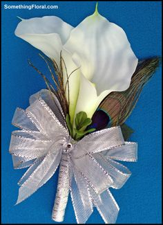 One of the realistic, artificial calla lily and peacock feather, pin-on style corsages custom created by Something Floral/Something Spectacular for the mothers of the bride (Debbie) and groom (Bob). #calla #lily #corsage #wedding #flowers #corsages #peacock #feather #silver #ribbon #white #blue Available for custom order from our studio or SomethingFloral Etsy store.