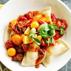 Pierogies with Meat Sauce  For a budget-friendly meal, cook chorizo sausage with cherry tomatoes and tomato sauce, and then spoon over potato- and onion-filled pierogies.