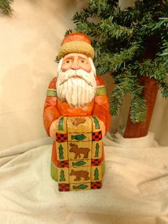Hand carved wood Old world Santa figure holding a lodge style quilt by Dan and…