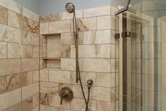 x Second shower area in this dual shower bathroom remodel has removable shower head with an easy reach to the built-in seat.
