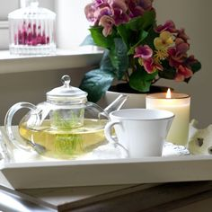 Calming bedroom tea area  Dusky pink flowers, a scented candle and a breakfast tray adorned with pretty white china and glass teapot, inject a calm feel into this bedroom.