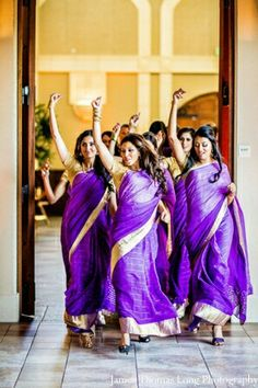 Purple bridesmaid sarees with a gold border stand out for these bridesmaids making a grand entrance