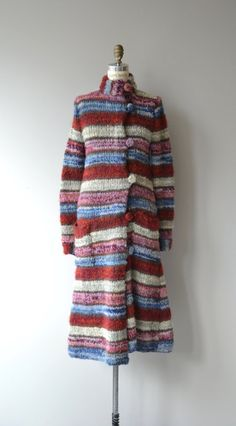 Amazing 1970s hand knit wool sweater coat with mock collar, asymmetrical kit buttons and hip pockets. Unlined and quite soft. --- M E A S U R E M E N T S ---  fits like: medium shoulder: 17 bust: up to 40 waist: uo to 40 hip: up to 42 sleeve: 27 length: 47 brand/maker: n/a condition: excellent  ★ layaway is available for this item  ➸ More vintage coats http://www.etsy.com/shop/DearGolden?section_id=5800175  ➸ Visit the shop http://www.DearGolden.etsy.com _____________________  ➸ instagram…