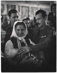 [Army officer and a young mother holding a baby during a baptism ceremony, Andartikon, Florina, Greece] 1950. Copyright © David Seymour/Magnum Photos