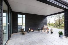 an exciting concrete veranda with classic wooden chair in an enchanting black wooden house with glass window and natural surroundings