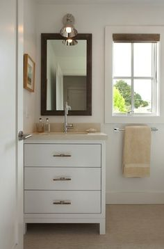 Chic small bathroom design with modern white washstand bathroom cabinet vanity, quartz counter top, modern polished nickel gooseneck faucet, espresso stained beveled wood mirror, bamboo orman shade and polished nickel sconce.