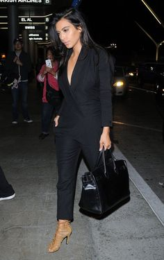 Kim Kardashian Jumpsuit - Kim Kardashian caught a flight at LAX looking ultra stylish in a black tuxedo-style jumpsuit by Saint Laurent.