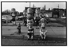 Description	Black and white photographic print mounted on board depicting people dressed in costumes with oversized heads as girls in dresses and boys in knickers gathered at a parking lot on the northwest corner of Woodward Avenue and W Ferry Street during the Thanksgiving Parade. Two people, one dressed as a boy and the other as a reindeer, sit next to each other on the curb. In the background is the Richard Cohn Building on the campus of Wayne State University. Date	1973 Woodward Avenue, Wayne State University, Detroit History, Thanksgiving Day Parade, People Dress, Parking Lot, North West, Reindeer, New York City