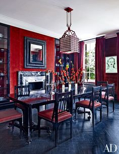 A dining room with red walls and a 18th century table refinished in black lacquer | archdigest.com