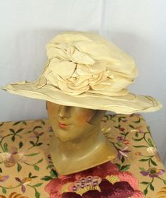 "Lovely wide brim hat from the early to mid-1920s is fashioned of cream silk, with a soft, deep cloche crown. Tagal straw braid facing stiffens the underbrim, which is slightly wider at the sides than in front and back. The hat is trimmed in front with a charming silk and charmeuse flower with charmeuse-wrapped wire ""stem"" and three petals.  Lined in cream silk satin, the hat has no label but has been stamped ""The Greenwich Sport Shop, 95 E. Putnam Ave Greenwich Conn"""