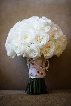A white rose round bouquet with a beaded wrap | Brides.com