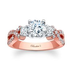 """Rose Gold Engagement Ring - This classic engagement ring is made with rose gold and white trim. It has a prong set round diamond center flanked with side diamonds and a crisscrossing shank set with shared prong set diamonds gracing the ridges. Also available in 14k white gold, 18k and Platinum."""