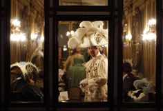 Masked revellers stand inside Caffe' Florian coffee shop in Saint Mark's Square during the Venetian Carnival in Venic