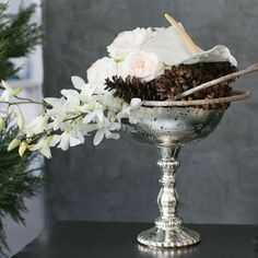 Gorgeous scalloped silver mercury glass pedestal glass bowl in silver. This wedding decoration measures 8 inches tall and 7 inches in diameter. Create a flower arrangement in this silver bowl to make a stunning wedding centerpiece.