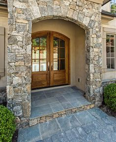STUNNING stone arched entryway and double wood doors.