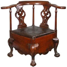 """Mahogany Chippendale Commode Stool, c.1760. This commode stool, which would otherwise appear to be a corner chair, is quite low to be a corner chair and meant, through its deep skirt, to hold a potty insert, which is now gone. It retains its original embossed leather seat with rosehead nails, etc. It has beautifully shaped arms with what appear to be owl eye splats, all of which are supported on four carved claw and ball feet. Note skirt is is also beautifully shaped. The """"Master's"""" commode!"""
