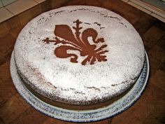 """Schiacciata alla Fiorentina (credits: Tuscanycious and fudzu on Flickr). Made with a base of pasta and bread that is sweet, soft, and light. The dough is made using simple ingredients, in which the Tuscan olive oil takes the place of butter or lard. Widely consumed during Carnival, it is covered with icing sugar and with a """"Giglio"""" (lily) of Florence in cocoa at the centre."""