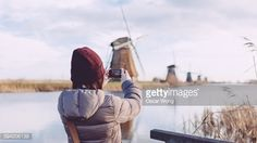 Stock Photo : Girl taking picture of windmills with smartphone