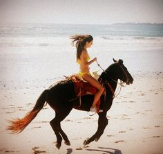 16 year old reality TV star and model Kendall Jenner in a yellow bikini riding a horse at the beach 2