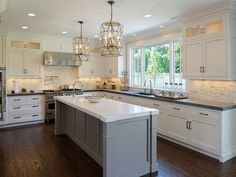 Gorgeous light kitchen with white cabinets, hardwood floors, gray island and chandelier pendants.