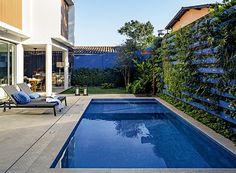 Área de lazer com churrasqueira, piscina e jardim em casa de praia