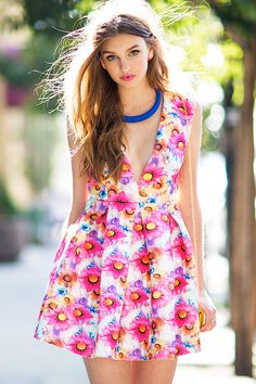BOUTIQUE FIVE A bright neoprene flare dress, featuring a bold floral print and a plunging v-neck. Sleeveless. Open back with a button loop and concealed zip closure. Defined waist. Pleated skirt. Short raw cut hem. $44.90