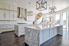 Stunning and spacious white kitchen with two kitchen islands, statement lighting and waterfall granite counters.
