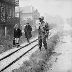 French civilians pass a British military policeman of No. 6 Beach Group in La Brèche d'Hermanville, 6 June 1944.