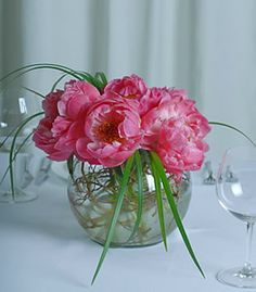 Delightfully delicate, these coral pink peonies are arranged in a round bubble bowl vase and accented with lily grass.