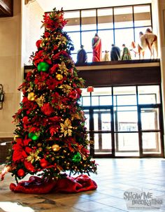 Traditional Christmas tree. Poinsettia christmas tree. Red, green, and gold christmas ornaments.
