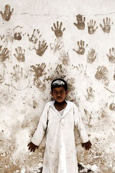 Boy in front of a wall with hand prints - Sanaa - Yemen by Eric Lafforgue, via Flickr