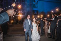 The couple make their grand exit with a wedding sparkler send-off from their guests. Wedding Photographer: Red Trolley Studio.