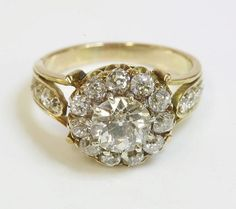 H0961-L65138290.jpg (750×667) Description: An Edwardian diamond cluster ring,with a central old European cut diamond, estimated as approximately 1.19ct. An outer row of old European cut diamonds to a scalloped gallery, with fleur-de-lys shoulders, inset with a line of graduated old European cut, Swiss cut and rose cut diamonds. Principal diamond assessed as approximately.Colour: J/KClarity: SI1/SI2Finger size M½