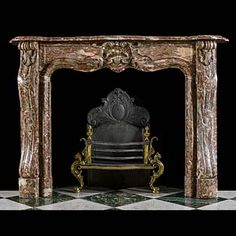 14316: A Louis XV Rococo style antique fireplace surround in very fine Rouge Royal Marble, with a simple moulded shelf above an elaborate central cartouche on the panelled frieze and with angled jambs flanki