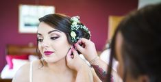 Side bun bridal hair with roses and gypsophilia. Romantic bridal make up cherry lipstick