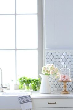 White kitchen with tiled backsplash with gorgeous bouquet of roses