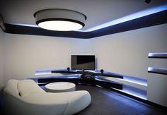 salon ultra moderne et blanc aménagé avec un meuble tv d'angle et niches de rangement lumineuses